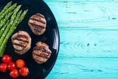 Grilled filet mignon with asparagus and tomatoes. Beef sreak on rustic background royalty free stock photography