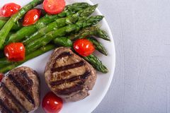 Grilled filet mignon with asparagus and tomatoes. Beef sreak on rustic background stock photography