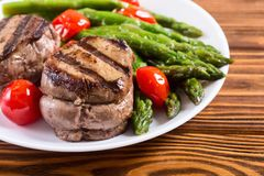 Grilled filet mignon with asparagus and tomatoes. Beef sreak on rustic background royalty free stock photos