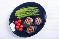 Grilled filet mignon with asparagus and tomatoes. Beef sreak on rustic background stock image