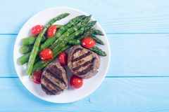 Grilled filet mignon with asparagus and tomatoes. Beef sreak on rustic background royalty free stock images
