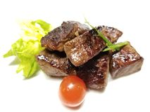Grilled Filet Mignon Cubes. Delicious and tender Filet Mignon cubes on a white background, with trimmings stock photo