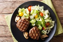 Grilled filet mignon steak with vegetable salad and mushrooms cl. Ose-up on a plate on the table. horizontal top view from above royalty free stock images