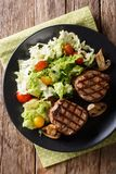 Grilled filet mignon steak with vegetable salad and mushrooms cl. Ose-up on a plate on the table. Vertical top view from above royalty free stock photo