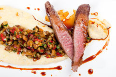 Grilled fillet of lamb with polenta, vegetables, spice and gravy Stock Photos