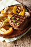 Grilled fillet mignon with potato wedges and mushrooms close-up. On a plate on a table. vertical Royalty Free Stock Images