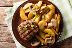 Grilled fillet mignon with potato wedges and mushrooms close-up. On a plate on a table. horizontal top view from above stock photography