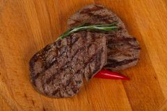 Grilled Fillet Mignon with rosemary and chili pepper. Over the wooden background stock photos