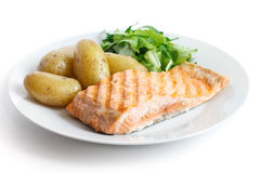 Grilled fillet of salmon on plate with green salad and potatoes Stock Photos