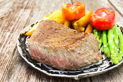 Grilled fillet steak served with tomatoes and roast vegetables Royalty Free Stock Photos