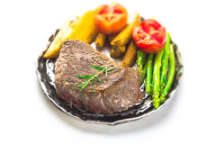 Grilled fillet steak served with tomatoes and roast vegetables Stock Photo
