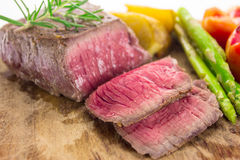 Grilled fillet steak served with tomatoes and roast vegetables Stock Images