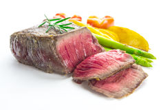 Grilled fillet steak served with tomatoes and roast vegetables Royalty Free Stock Photography