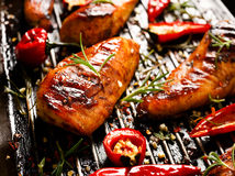 Grilled fillets of chicken in spicy marinade with the addition of chili on a grill pan royalty free stock image