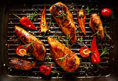 Grilled fillets of chicken in spicy marinade with the addition of chili on a grill pan royalty free stock photo