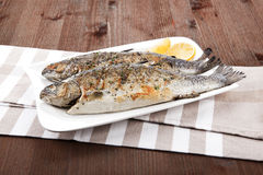 Grilled fish. Grilled trout on white plate with lemon pieces on kitchen towel on wooden table Stock Image