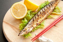 Grilled fish. With lemon and red chopsticks on a wooden cutting board royalty free stock image