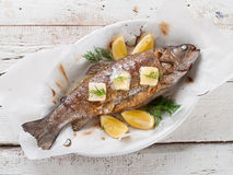 Grilled fish. With butter and lemon, selective focus Stock Image
