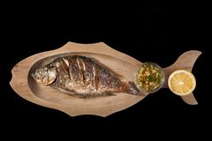 Grilled Fish Dorado with Lemon On a black background. Copy space. Stock Image