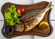 Grilled fish & x28;Dorado& x29; on a wooden board with lemon, salad, sauce and cherry tomatoes. Grilled fish & x28;Dorado& x29; on a wooden board with Royalty Free Stock Photography