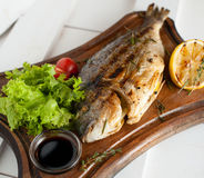 Grilled fish & x28;Dorado& x29; on a wooden board with lemon, salad, sauce and cherry tomatoes. Grilled fish & x28;Dorado& x29; on a wooden board with Royalty Free Stock Photos