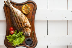 Grilled fish & x28;Dorado& x29; on a wooden board with lemon, salad, sauce and cherry tomatoes. Grilled fish & x28;Dorado& x29; on a wooden board with Royalty Free Stock Photo