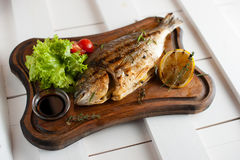Grilled fish & x28;Dorado& x29; on a wooden board with lemon, salad, sauce and cherry tomatoes. Grilled fish & x28;Dorado& x29; on a wooden board with Stock Images