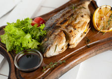 Grilled fish & x28;Dorado& x29; on a wooden board with lemon, salad, sauce and cherry tomatoes. Grilled fish & x28;Dorado& x29; on a wooden board with Stock Image