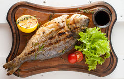 Grilled fish & x28;Dorado& x29; on a wooden board with lemon, salad, sauce and cherry tomatoes. Grilled fish & x28;Dorado& x29; on a wooden board with Stock Photo