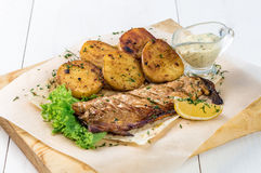 Grilled fish fillet with baked potatoes with sauce on a wooden board stock photography