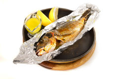 Grilled fish in foil uith lemon juice sauce in black pan on wood Stock Images