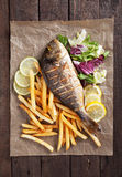 Grilled fish with french fries and salad Stock Images