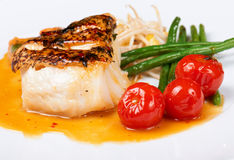 Grilled fish with garnish. Grilled fish with runner beans and cherry tomatoes on white plate Royalty Free Stock Photography