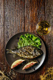 Grilled fish and glass of wine Stock Photos