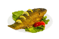 Grilled fish with greens on the plate, isolated Royalty Free Stock Image