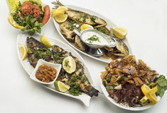 Grilled Fish with Lemon Slices, Grilled seafood served on plate isolated on white Royalty Free Stock Photo