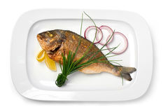 Grilled fish on a plate with onions and lemon Stock Photography