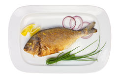 Grilled fish on a plate with onions and lemon Stock Images