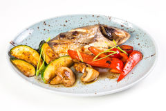 Grilled fish on plate. With grilled vegetables isolated on white Royalty Free Stock Photos
