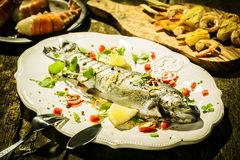 Grilled Fish on Platter Surrounded by Other Dishes Royalty Free Stock Photography