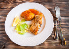 Grilled fish with potatoes, slice of lemon and red sause on wood Royalty Free Stock Images