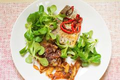 Grilled fish, roasted potato steipe and lamb´s lettuce stock images