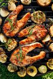 Grilled fish, grilled salmon steak with the addition of rosemary, aromatic spices and vegetables on the grill plate outdoors stock photos