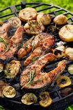 Grilled fish, grilled salmon steak with the addition of rosemary, aromatic spices and vegetables on the grill plate outdoors stock image