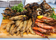 Grilled fish, shrimp, mussels and seafood sticks. Street food. Stock Photos