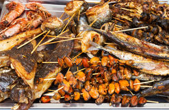 Grilled fish, shrimp, mussels and seafood sticks. Street food. Stock Images