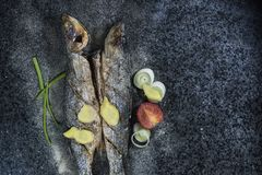 Grilled fish with spices, vegetables and herbs on slate background ready for eating. Grilled fish with spices, vegetables and herbs on slate background ready royalty free stock images