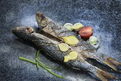Grilled fish with spices, vegetables and herbs on slate background ready for eating. Grilled fish with spices, vegetables and herbs on slate background ready stock photo