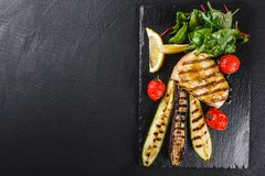 Grilled fish steak garnished with salad of spinach and grilled vegetables on shale background over dark background. Hot fish dish. Top view royalty free stock images