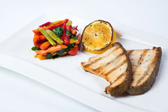 Grilled fish steak with lemon and vegetables Stock Images
